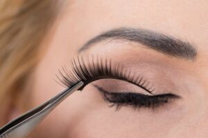 Applying false lashes with a tweezer