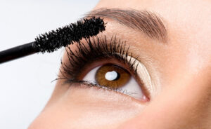 a model applying mascara to her lash extensions