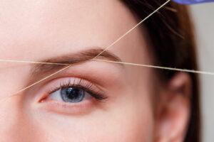 a woman getting her eyebrow threaded
